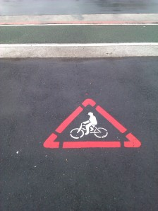 Warning stencilled at property exits to protect cyclists on cycle lane from leaving cars